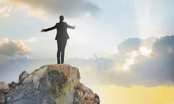 young woman standing on the top of rock and open hands towards the sun. success in business concept - szczyt zdjęcia i obrazy z banku zdjęć