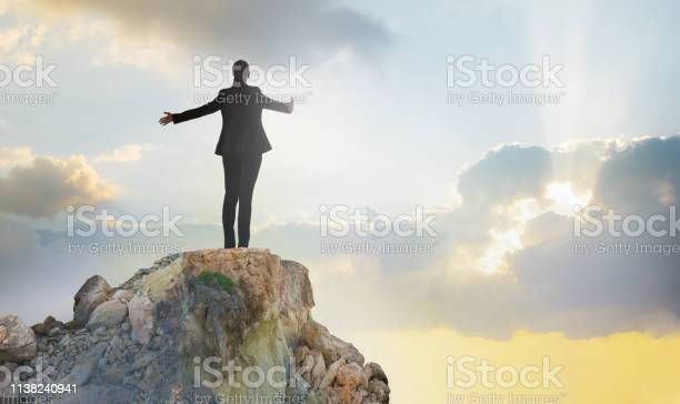 Photo of Young woman standing on the top of rock and open hands towards the sun. Success in business concept