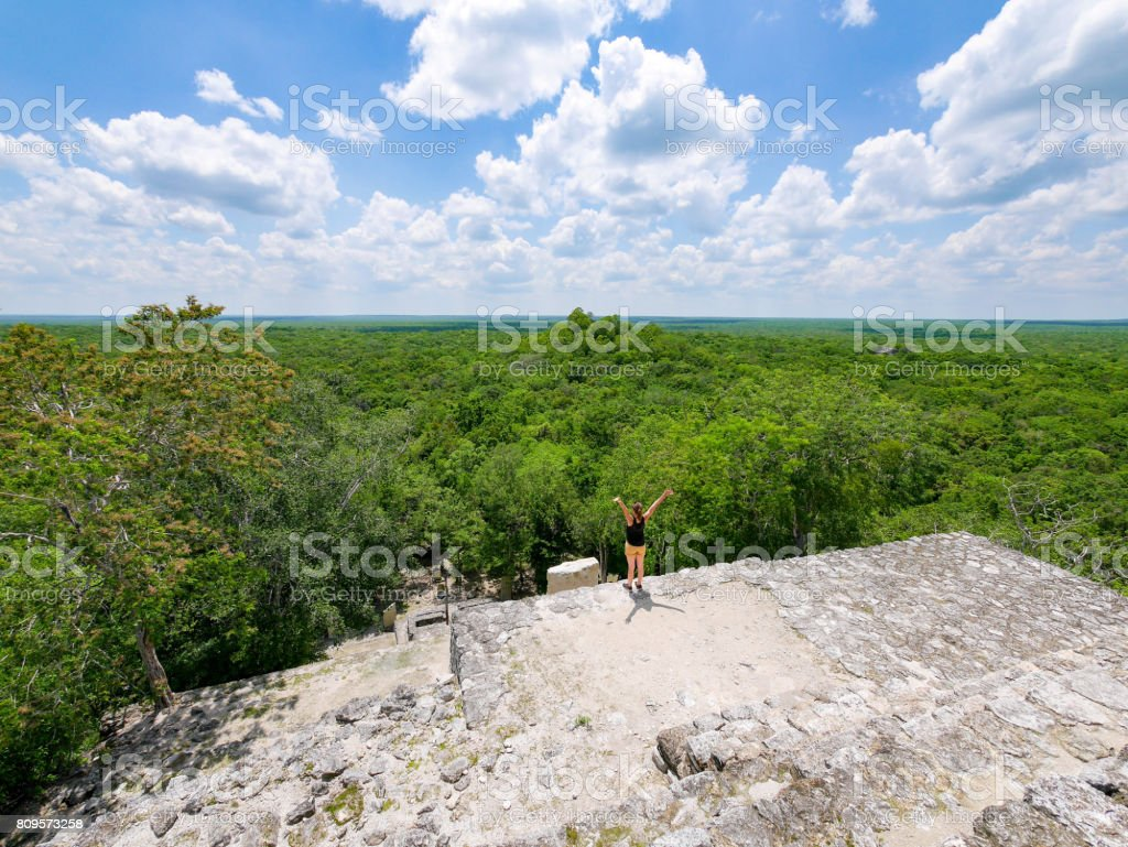 Young woman standing on top of maya temple ruin calakmul in mexico stock photo