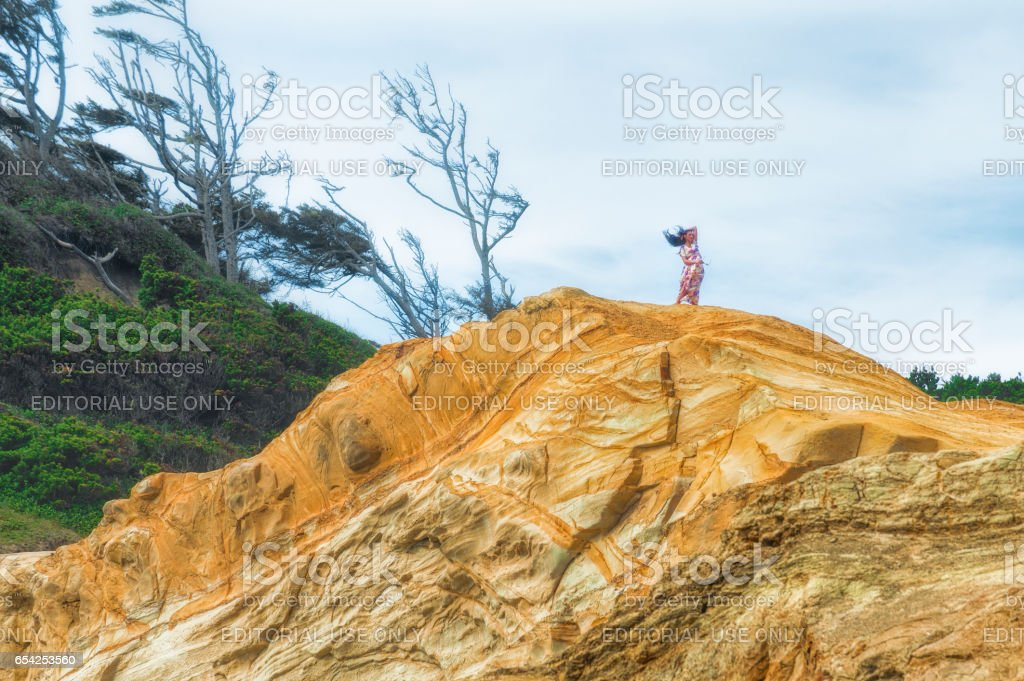Young woman standing on top of sandstone bluff at Cape Kiwanda stock photo