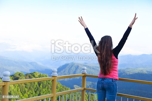 Young woman standing on viewing platform and looking into a wide valley. Caucasus. Russia