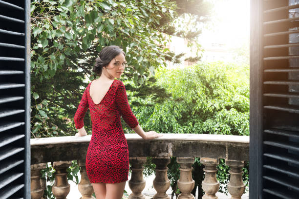 young woman standing on villa balcony - mini dress stock photos and pictures