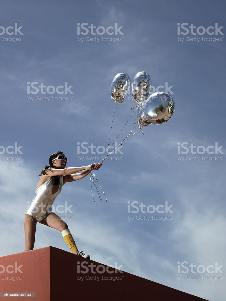 Young woman standing on wall holding helium balloon, low angle view royalty-free stock photo