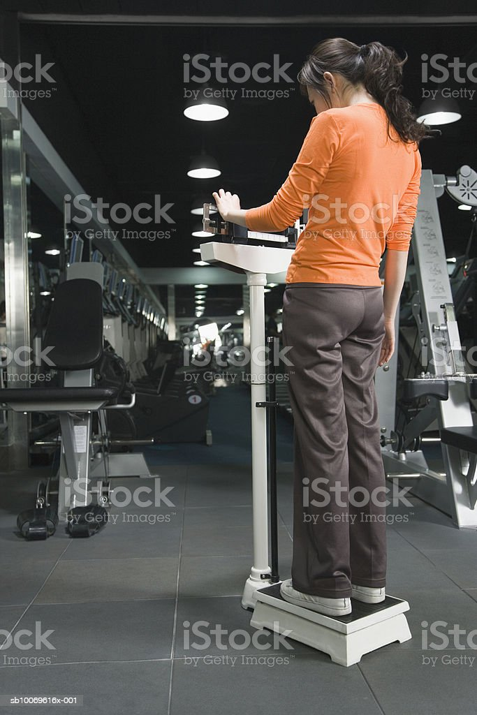Young woman standing on weight scale, rear view royalty-free stock photo