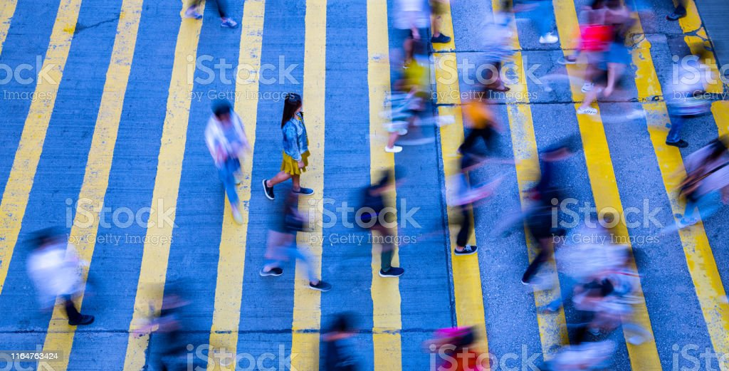 Young woman standing out, in motion blurred crowd