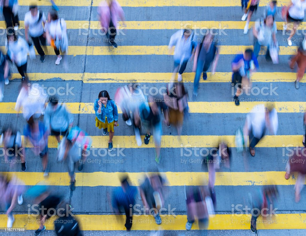 Young woman standing out, stationary in motion blurred crowd