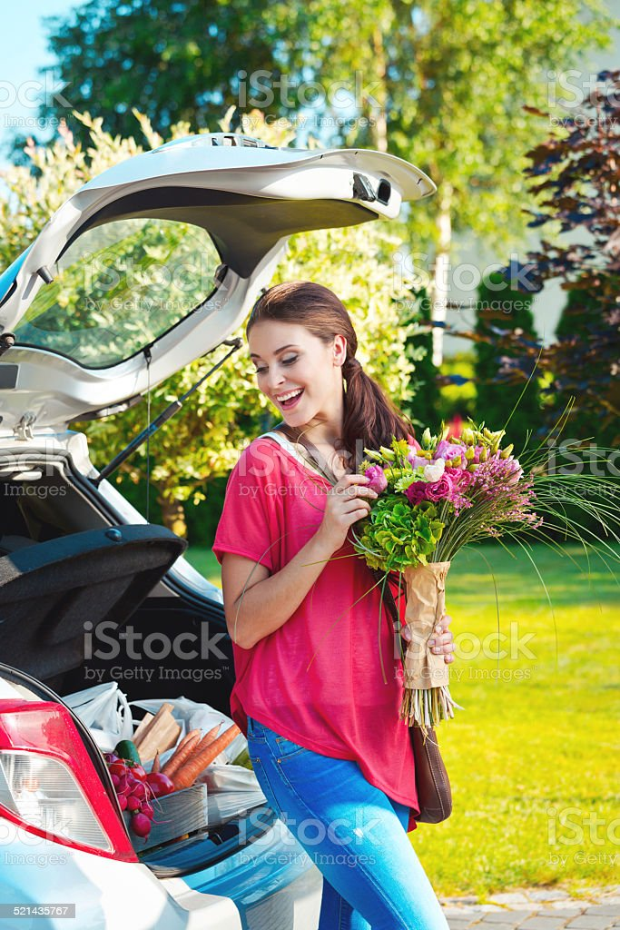Young woman standing outdoor by car, holding flowers Cheerful young woman came back from shopping, standing outdoor by the car trunk full of shopping bags and holding bouquet of flowers. 20-24 Years Stock Photo