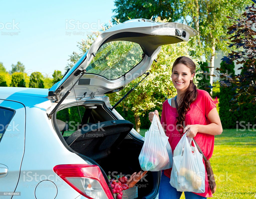 Young woman standing outdoor, holding shopping bags Cheerful young woman came back from shopping, standing outdoor by the car trunk and holding plastic bags full of groceries.  Adult Stock Photo