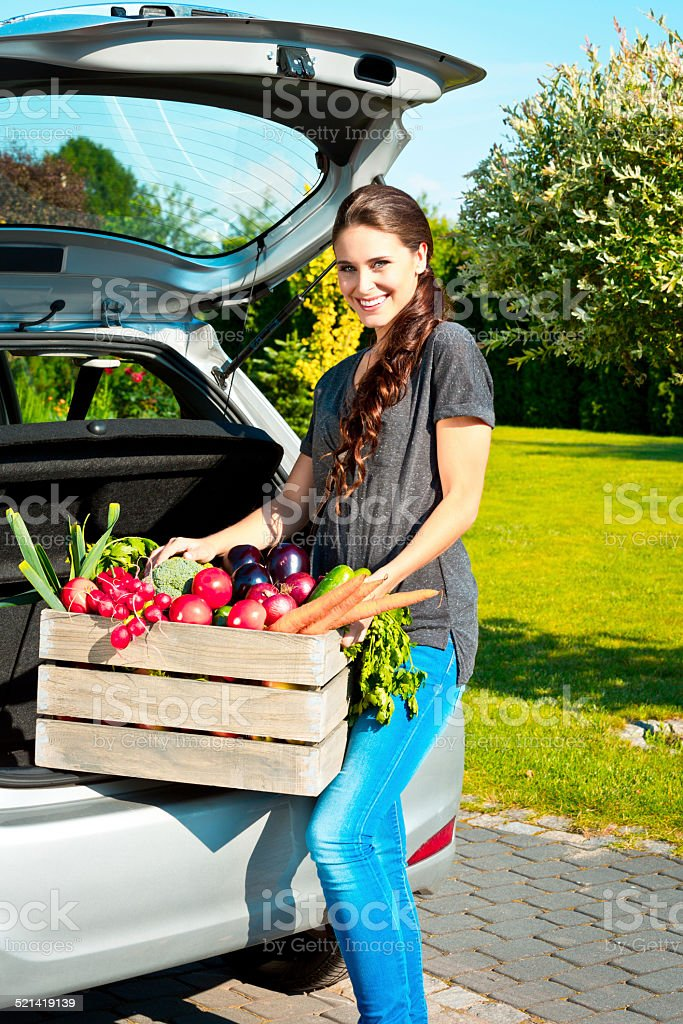 Young woman standing outdoor with box of vegetables Cheerful young woman standing outdoor by the car trunk and carrying the box of fresh vegetables. Adult Stock Photo