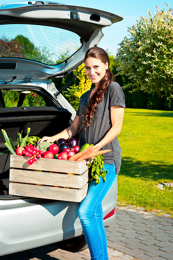 Young Woman Standing Outdoor With Box Of Vegetables Stock Photo - Download Image Now