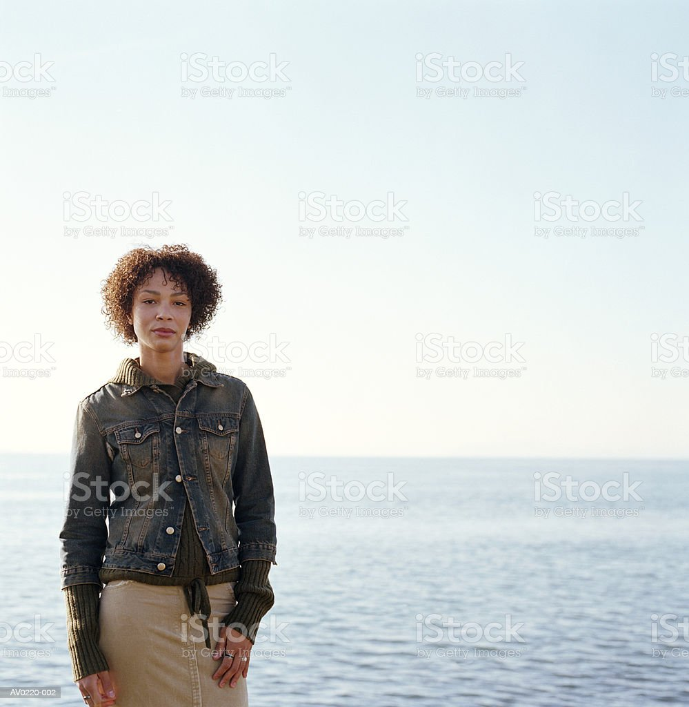 Young woman, standing outdoors, water in background royalty free stockfoto