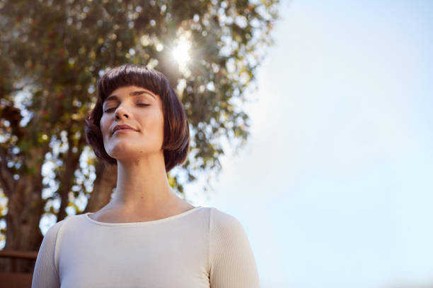 Young woman standing outside and meditating with her eyes closed stock photo