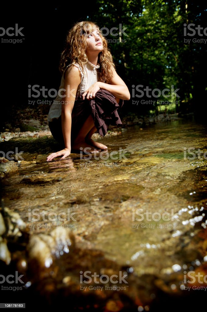 Young Woman Standing Small Stream in Forest royalty-free stock photo