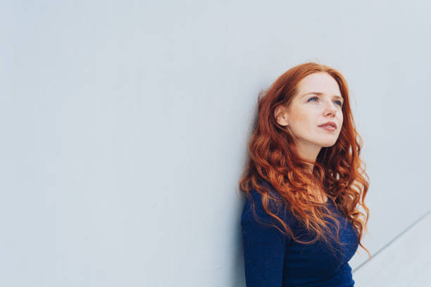 Young woman standing thinking deeply stock photo