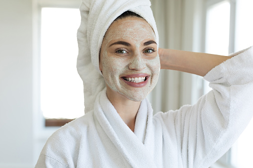 Young woman standing with a facial mask