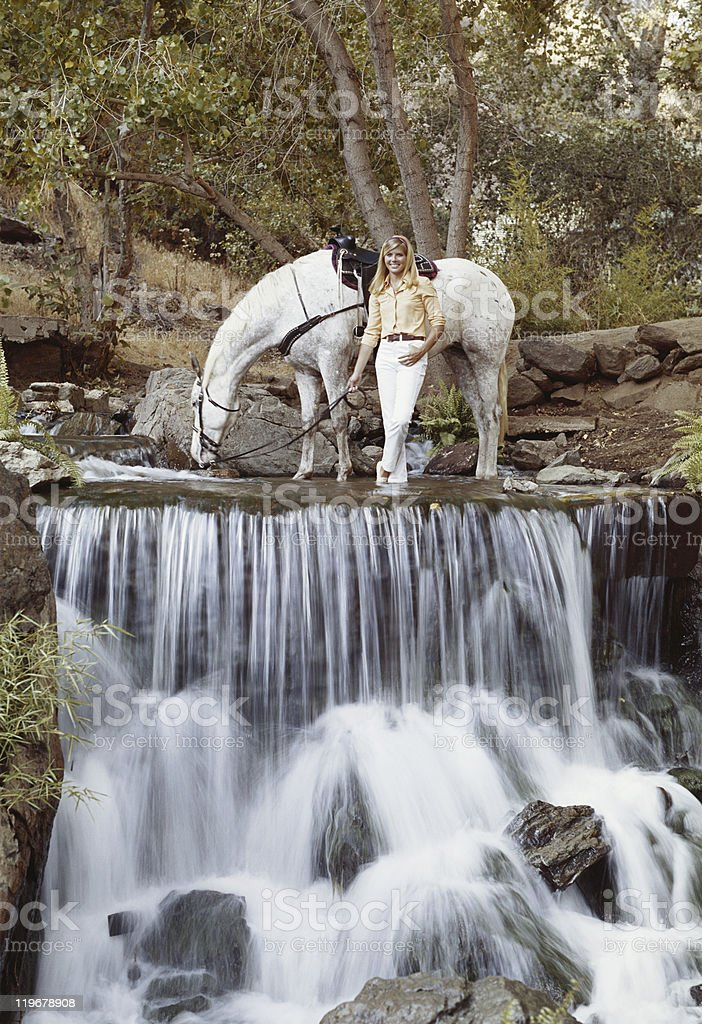Young woman standing with horse at edge of waterfall, smiling  stock photo