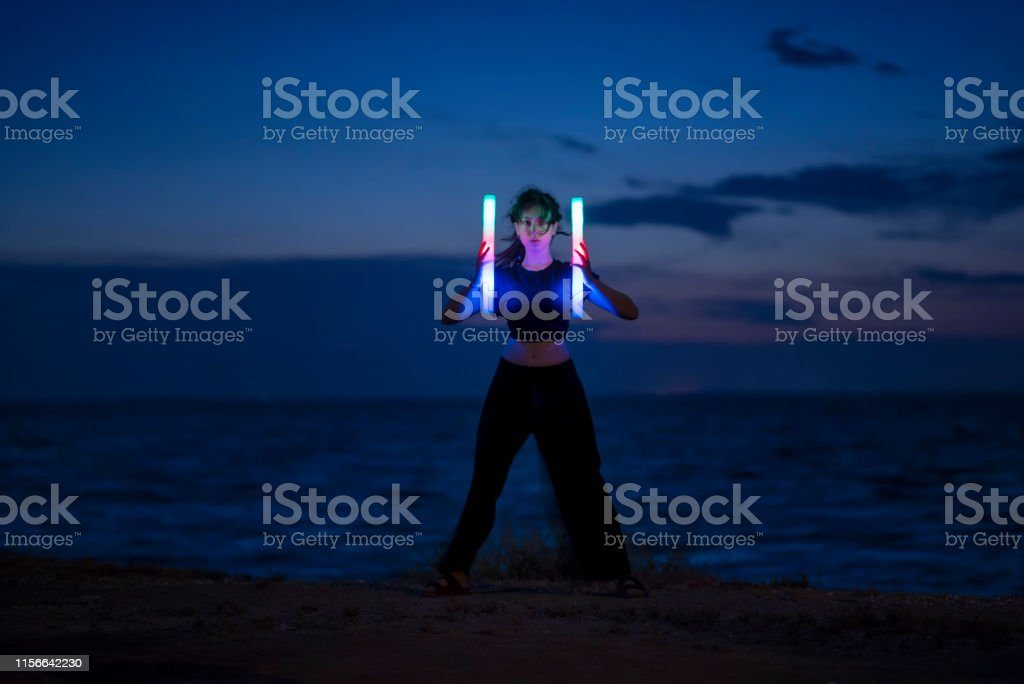 Young woman standing with lights by the sea.