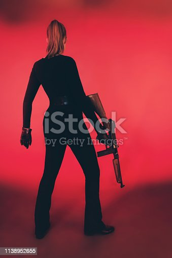 Young woman standing with machine gun against red background.