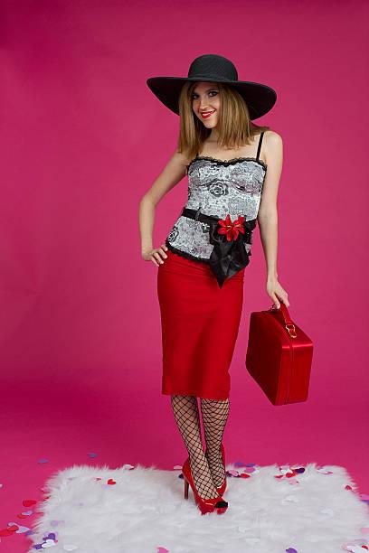 junge frau mit rotem satin-koffer - rote bleistiftröcke stock-fotos und bilder