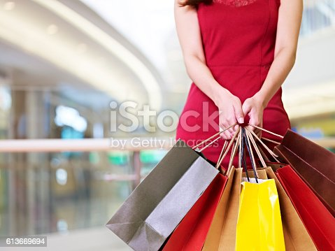 istock young woman standing with shopping bags in hands 613669694