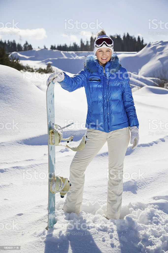 Young woman standing with snowboard in her nand and smiling stock photo