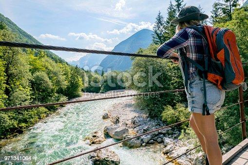 A young woman stands and looks at a hanging bridge, River Soca, Primorska,  Julian Alps,  European Alps, Slovenia, Europe,no logos,Nikon D850
