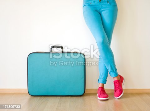 A young woman standing with a suitcase beside her.  The suitcase is an old-fashioned model and is blue with a black handle.  The suitcase is standing on its bottom edge with the handle sticking up.  The young woman is leaning against a white wall.  She is wearing blue pants and red tennis shoes with white soles.  Her right leg is crossed over her left leg.  Her left foot is flat on the ground.  The toes of the right foot are on the ground, but the heel is in the air.  The woman's body is only visible from the waist down.