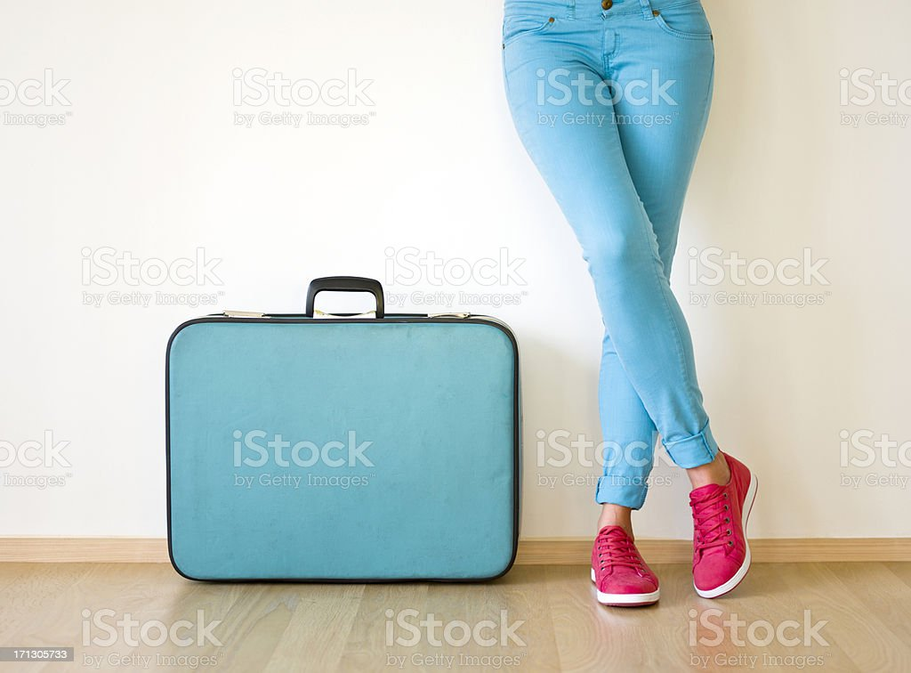 Young woman stands beside suitcase stok fotoğrafı