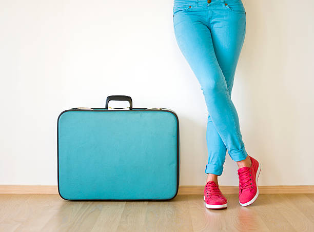 Young woman stands beside suitcase stock photo