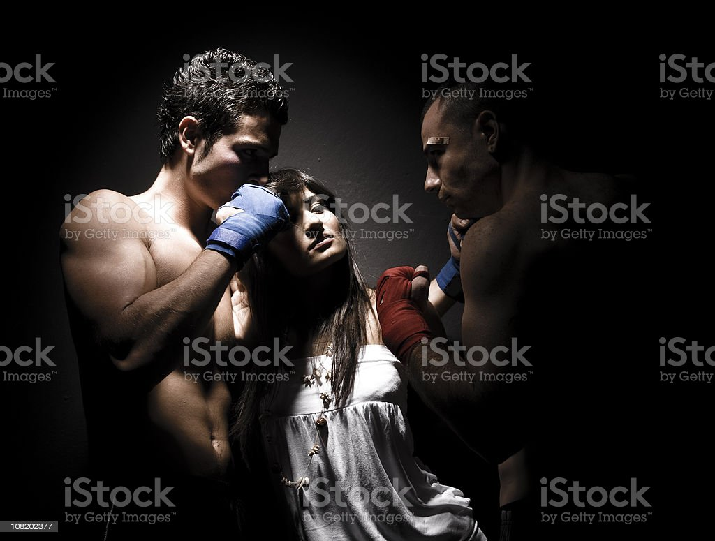 Young Woman Stands Between Two Men Ready to Fight royalty-free stock photo