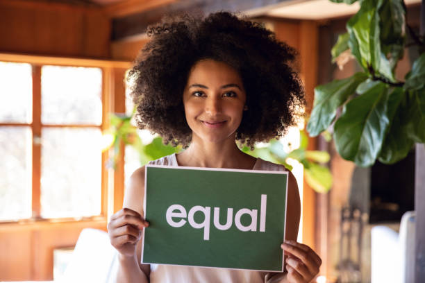 Young woman stands for equal rights. Young african american woman holding sign stands for equal rights. sex discrimination stock pictures, royalty-free photos & images