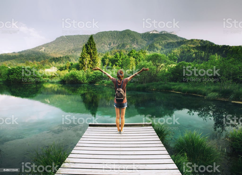 Young woman stands on a wooden bridge with raised arms up on the nature background. stock photo