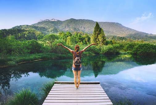 Young woman stands on a wooden bridge with raised arms up on the nature background. Travel, Freedom, Lifestyle concept. Slovenia, Europe.