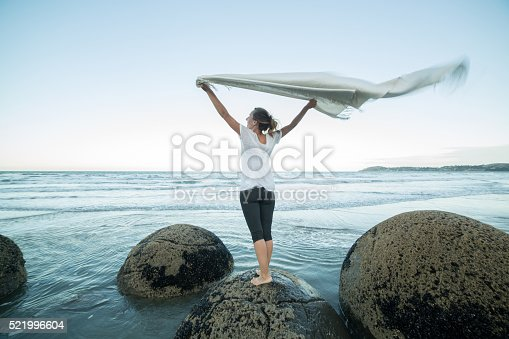 istock Young woman stands on boulder, holds blanket in the air 521996604