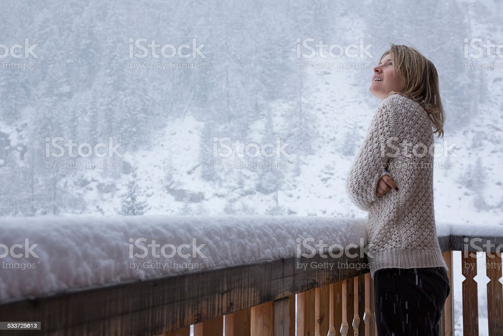 Young woman stands on deck, watches snowflakes fall during snows stock photo