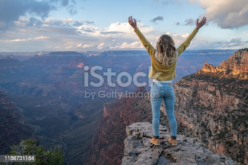 Young woman stands on top of canyon embracing life and nature arms outstretched  Girl enjoys hiking and travel USA