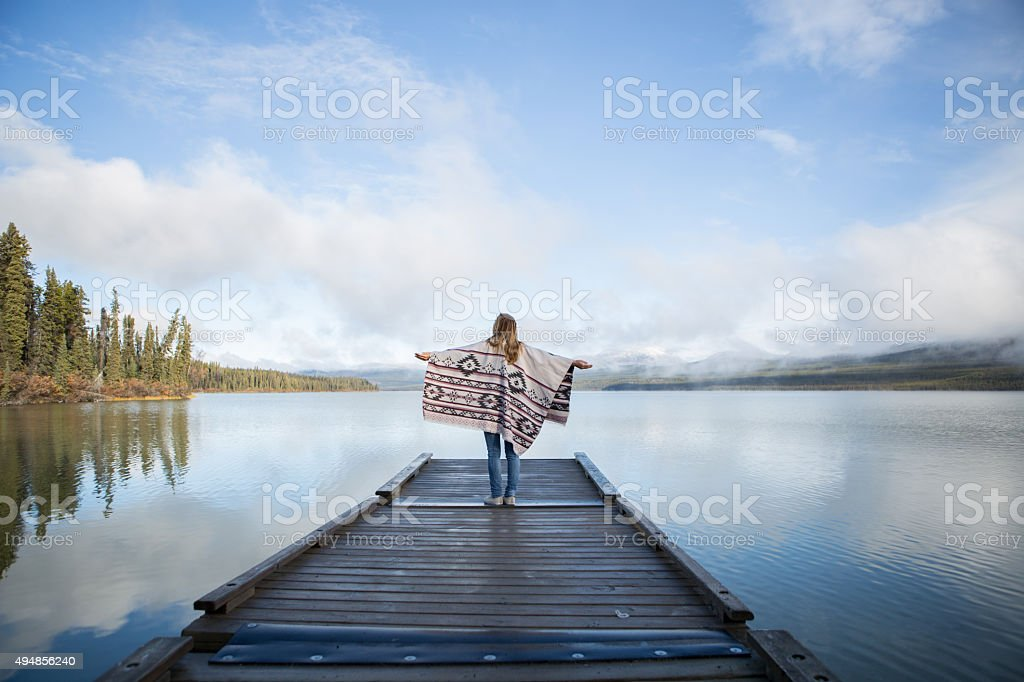 Young woman stands on wooden pier arms outstretched stock photo