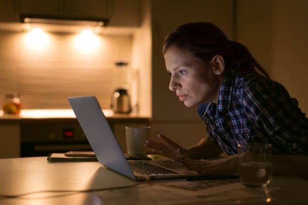 Jeune femme regarde fixement portable et travail - Photo