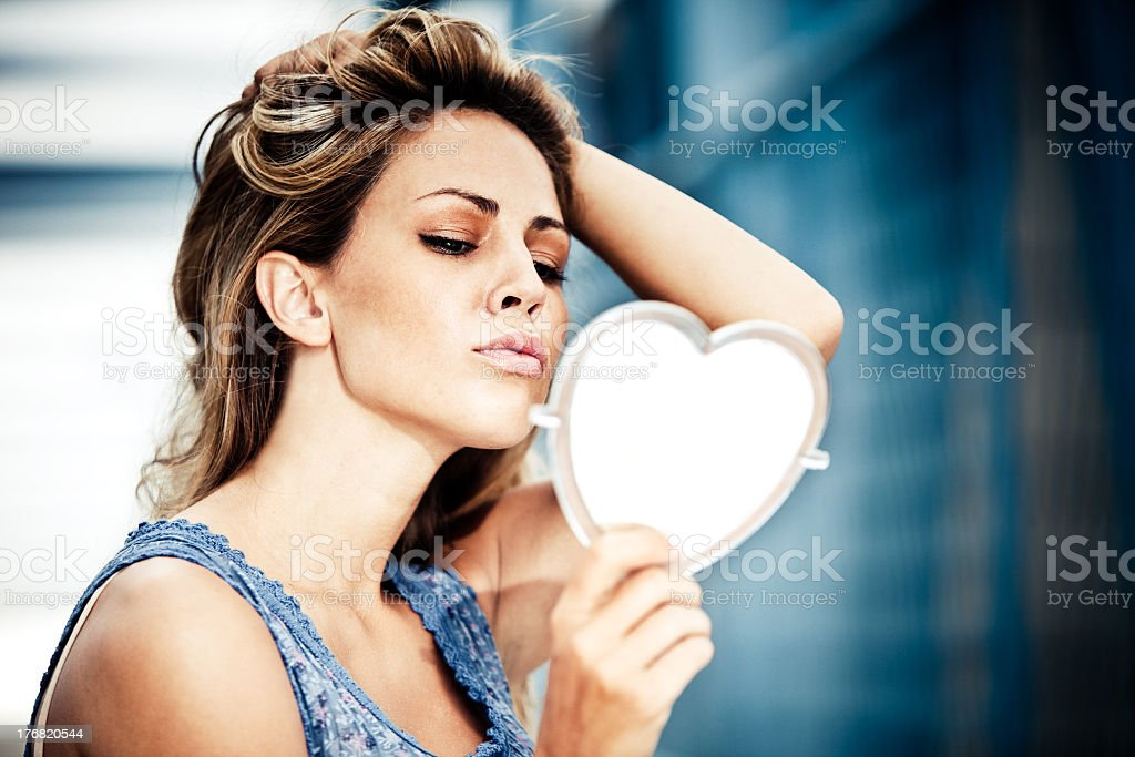 Young woman staring into a mirror holding her hair back stock photo