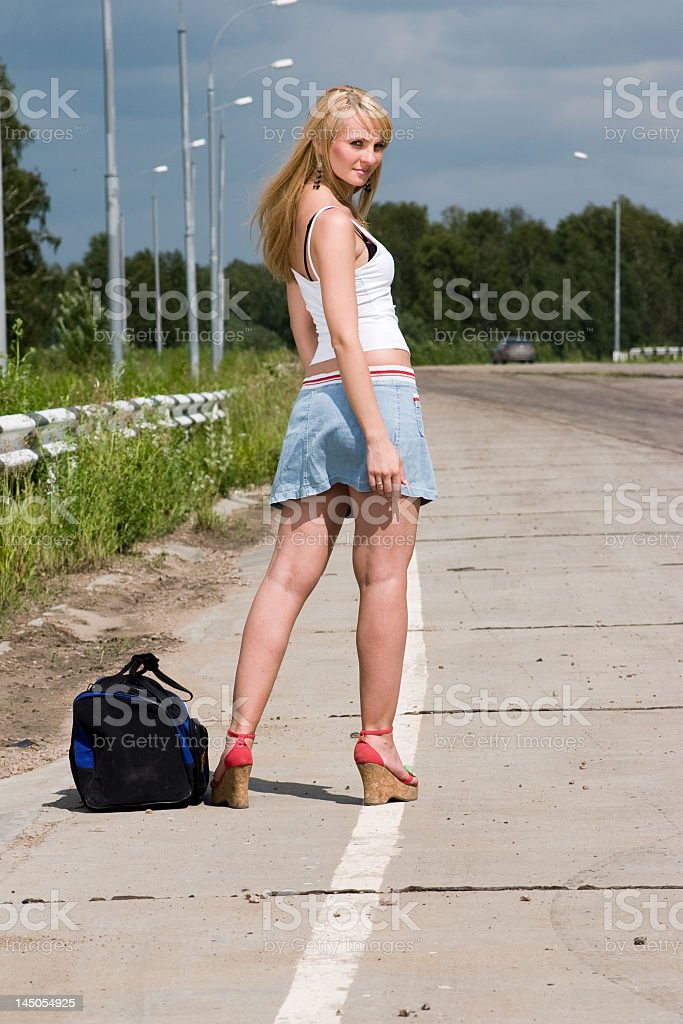 Young woman stay on the road. stock photo