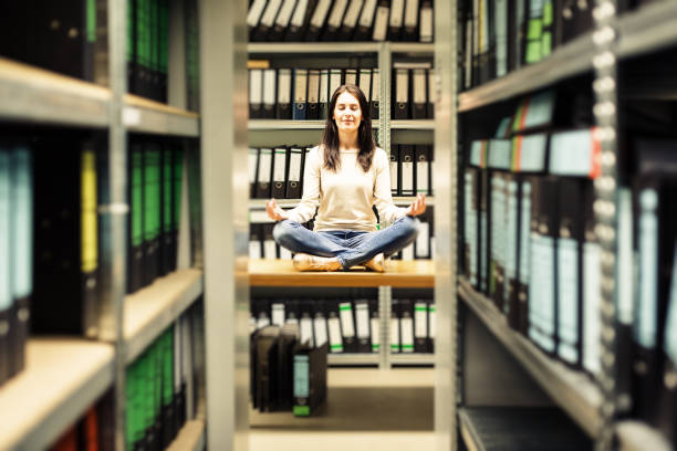 young woman staying calm amidst the chaos young woman / secretary is meditating and staying calm amidst the paperwork chaos amidst stock pictures, royalty-free photos & images
