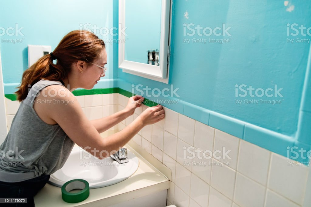 Young woman doing step by step DIY in small appartement bathroom....