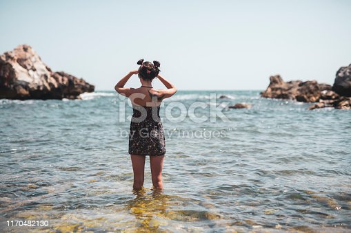 A young woman stepped into the seawater and looked forward.