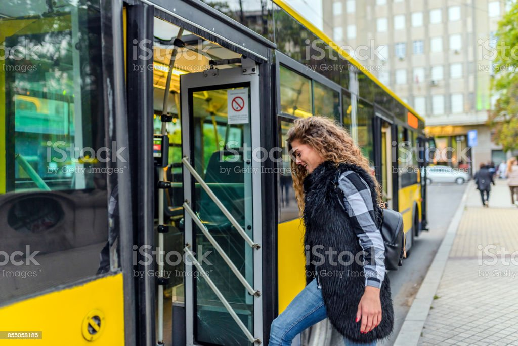 Young woman stepping into the bus stock photo