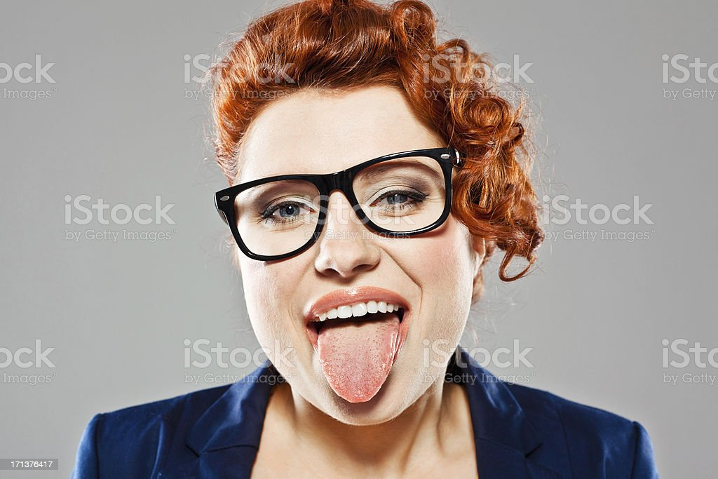 Young woman sticking out tongue Portrait of cute young woman sticking out her tongue, looking at the camera. Studio shot, grey background. 25-29 Years Stock Photo