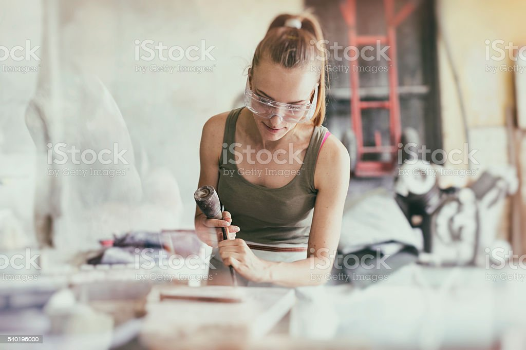 Young woman stonemason in her workshop stock photo