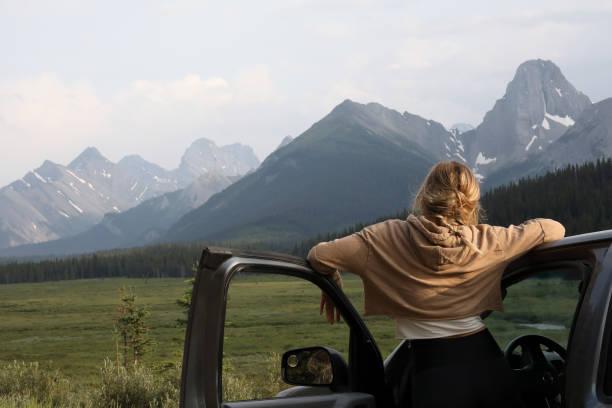 junge frau hält fahren zum entspannen und genießen den blick - serien schauen stock-fotos und bilder