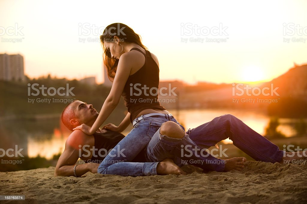 Young woman straddling man on river bank stock photo