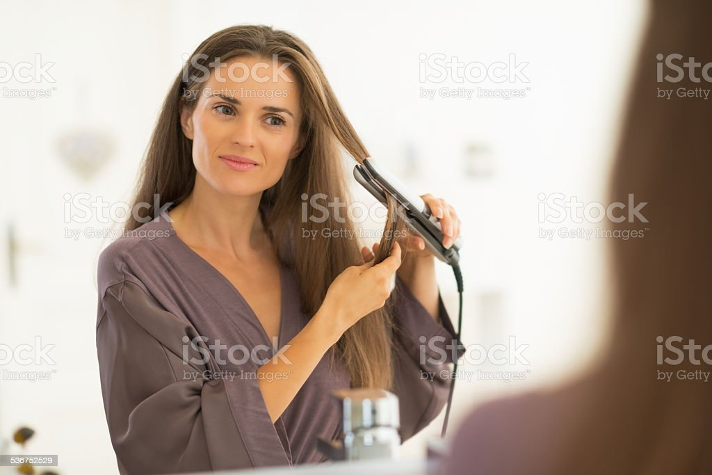 young woman straightening hair in bathroom stock photo
