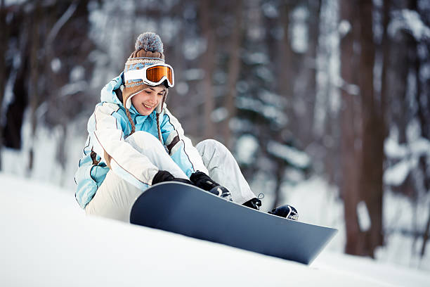 Young woman strapping in Young beautiful woman adjusts her bindings on snowboard sitting at ski slope ski goggles stock pictures, royalty-free photos & images